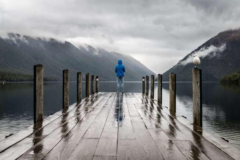 human looking at lake and mountains