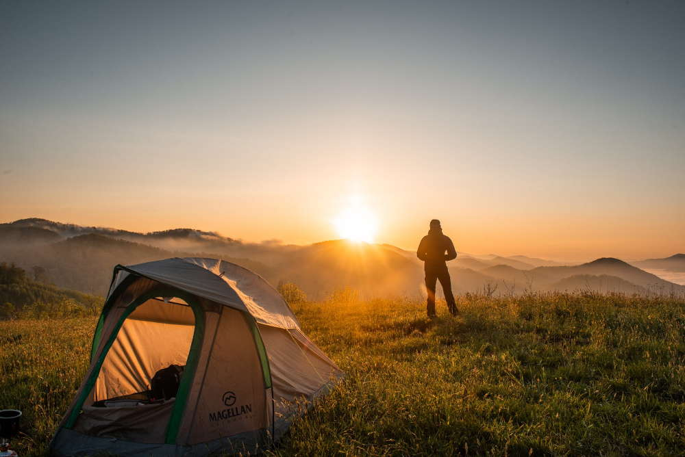 man looking at sun with tent behind him