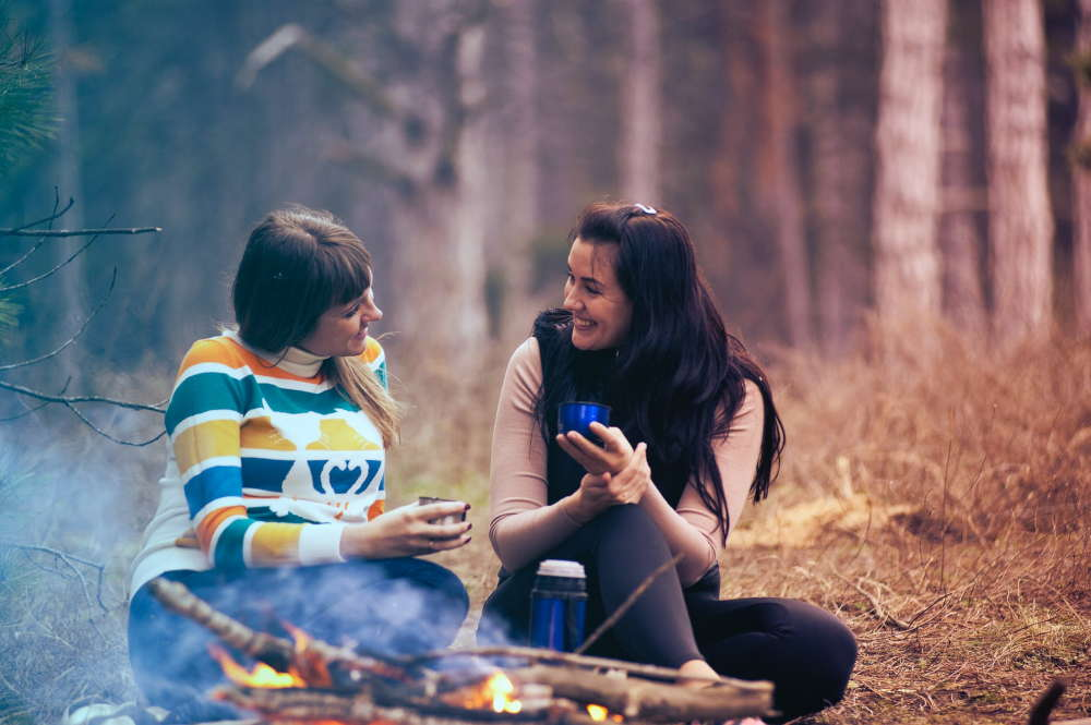 two woman drinking coffee and talking while camping